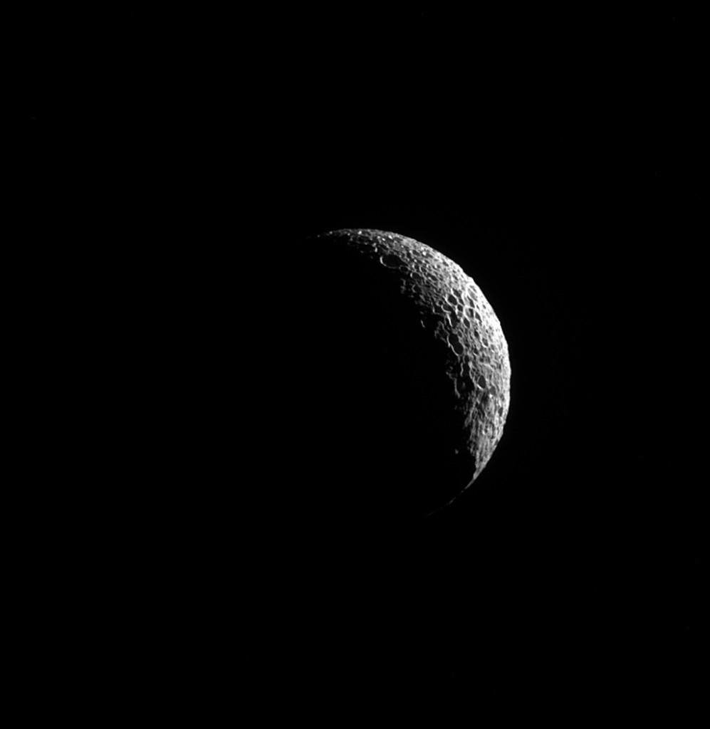 Mimas'ın bu görüntüsündeki krater çukurlarının göstergesi olan derin gölgeler, uydunun şiddet dolu geçmişini gözler önüne sermektedir.