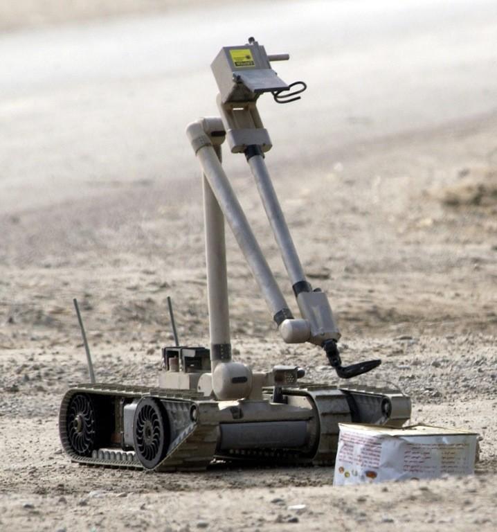 Amerika'nın patlayıcı madde imhası için kullandığı robotlardan biri Irak'ta ev yapımı bir bombanın telini çekerken.
